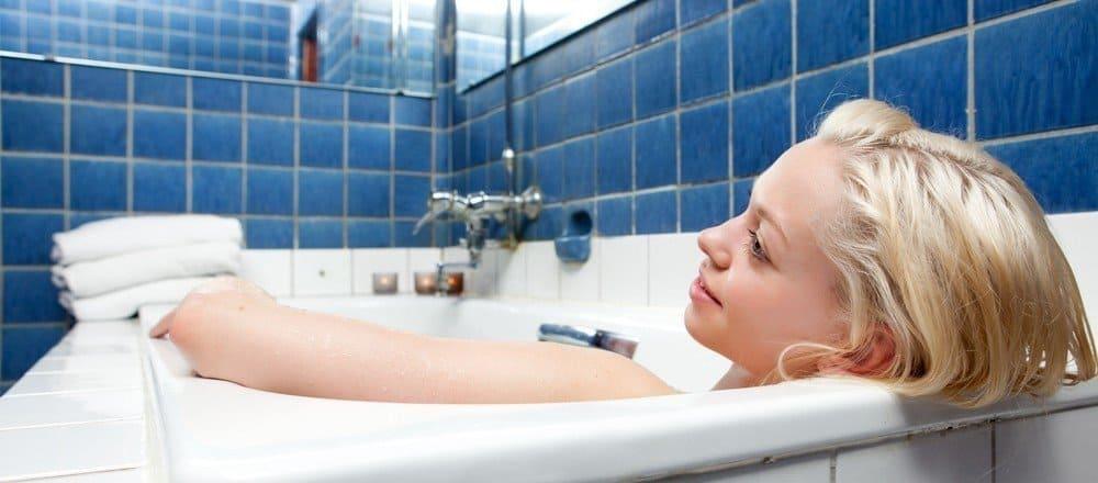 A woman enjoying a bath in a bathtub.