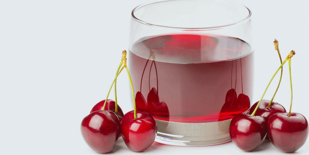 A glass of cherry juice with cherries next to it.