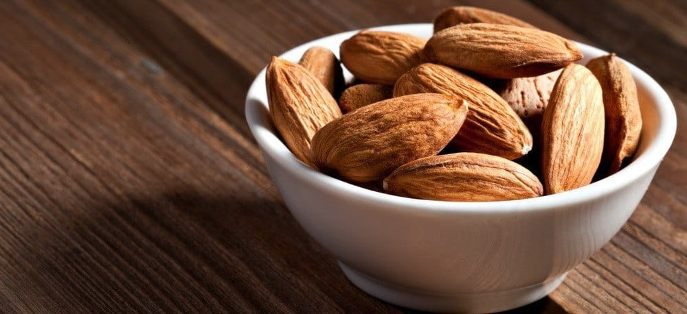 A handful of almonds in a cup.