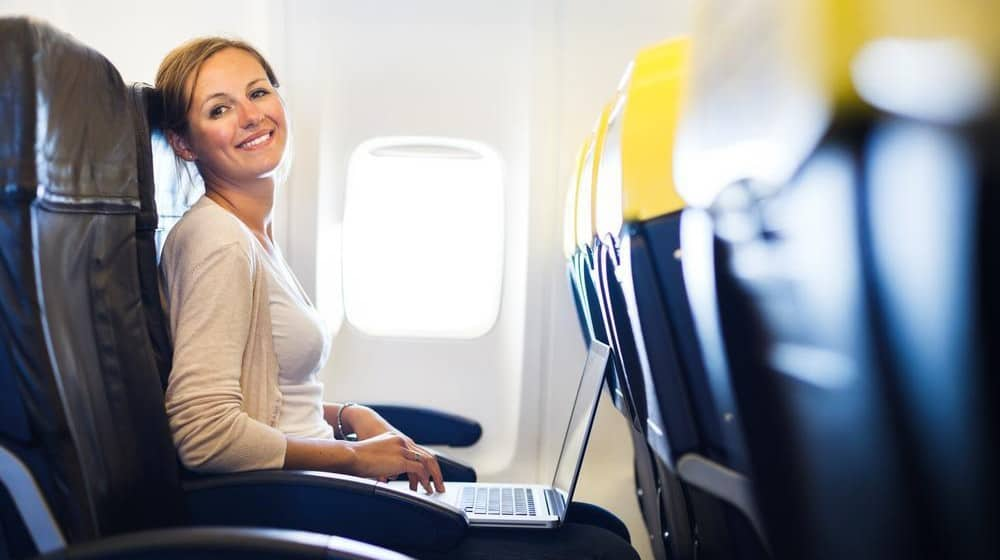 A woman smiling while sitting comfortably in an airplane seat.
