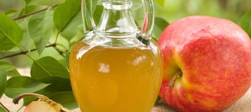 A small jug of apple vinegar next to apples and leaves.