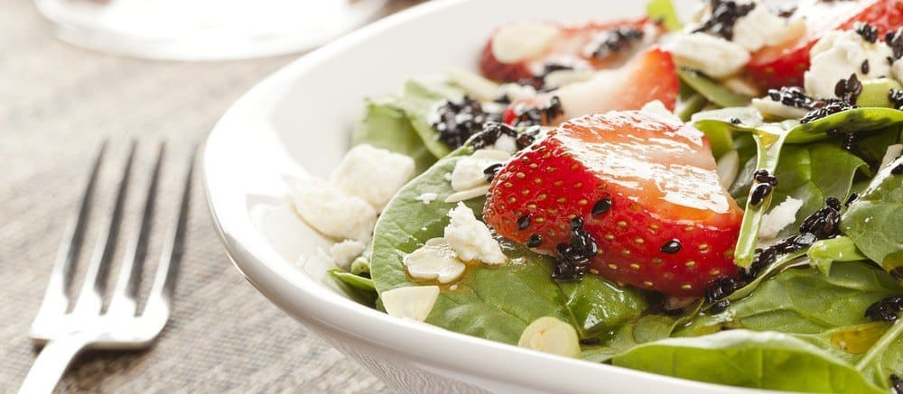 A plate of salad with various greens and a strawberry.