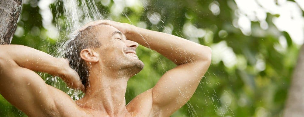 A man enjoying a refreshing shower outdoors.