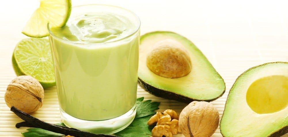 A glass of avoacado-based drink next to sliced avocados.