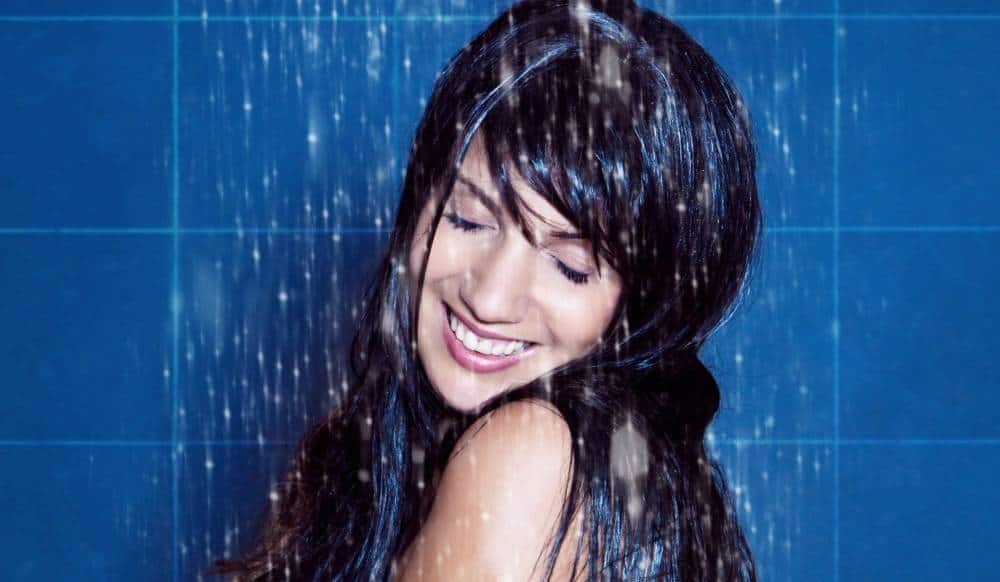 A young woman standing under a shower and smiling.