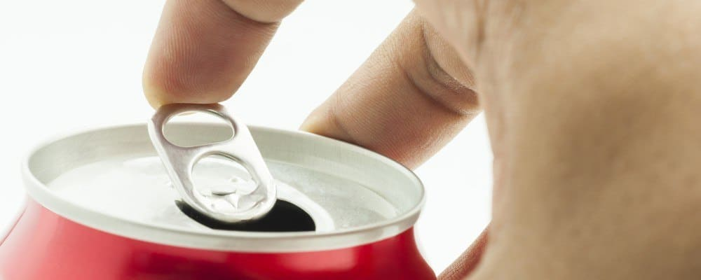 Close-up of a person's hand opening a can of soda.