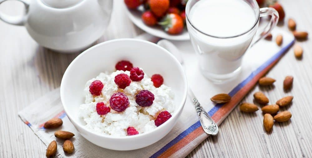 A bowl of cottage cheese topped with raspberries, next to a glass of milk.
