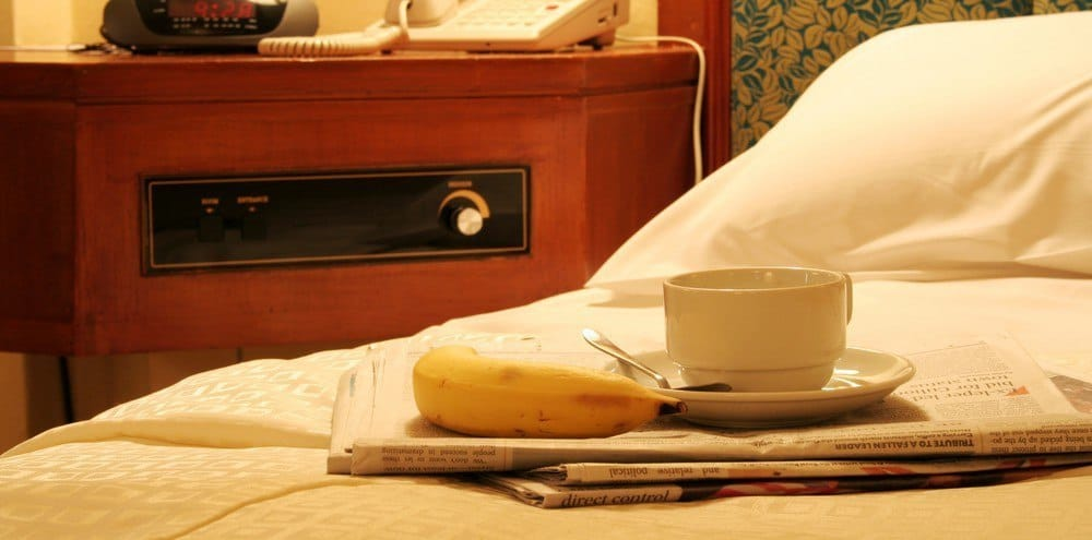 A banana with a cup of coffee placed on a stack of newspapers on a bed.
