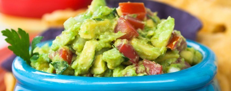 A bowl of guacamole and vegetables.
