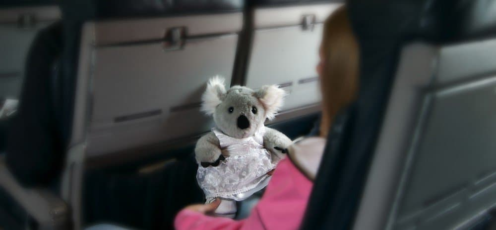 A small koala figure in an airplane seat.