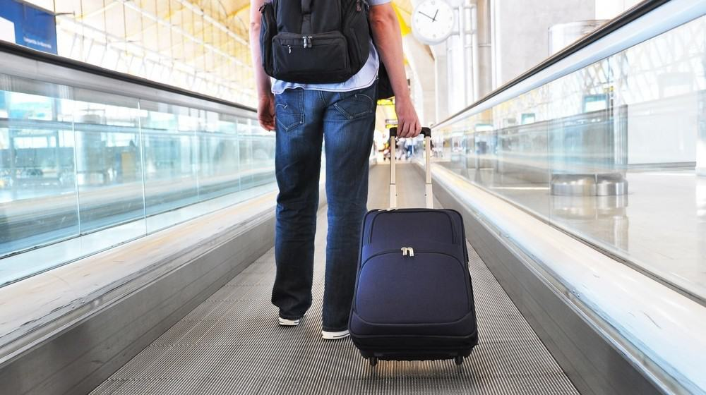 A man holding his luggage while standing on a moving walkway.