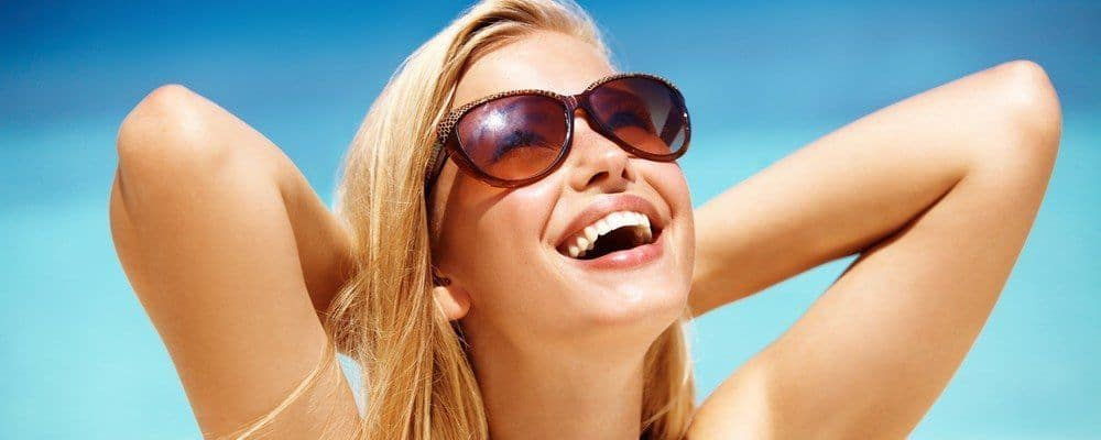 A woman in sunglasses laughing as she enjoys the bright sun in the open.