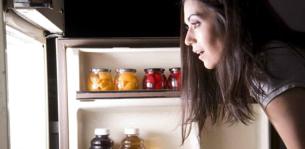 A woman eagerly looking into her fridge.