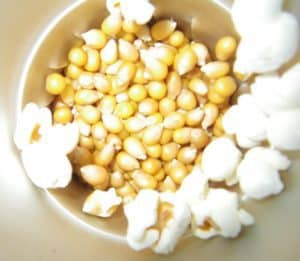 A cop of popcorn and corn kernels