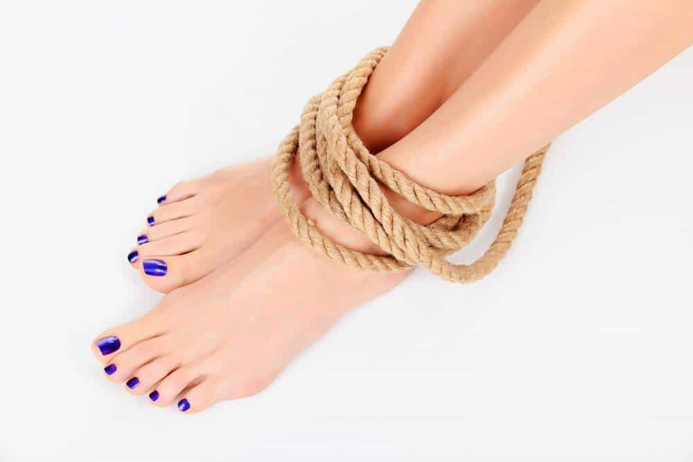 A woman's feet tied with a rope.