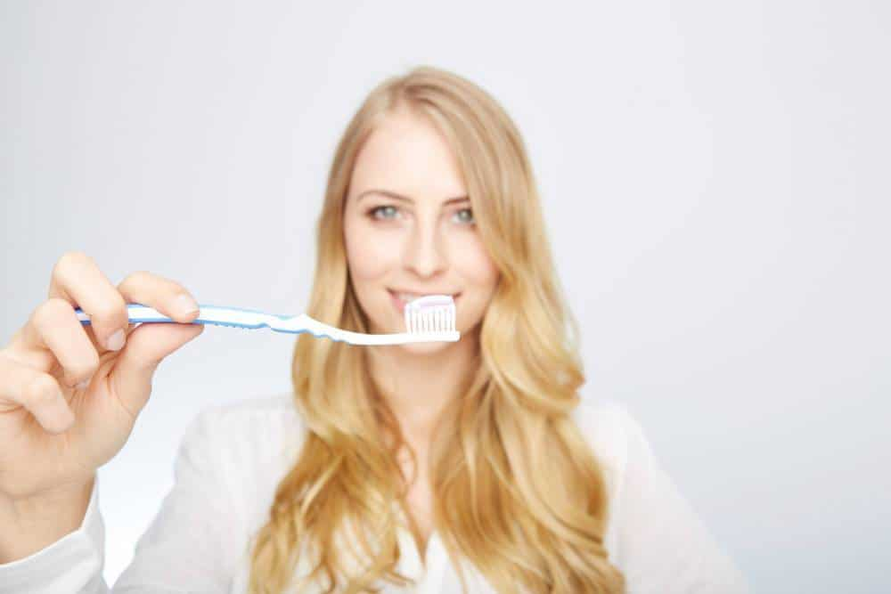A woman holding a toothbrush with toothpaste.