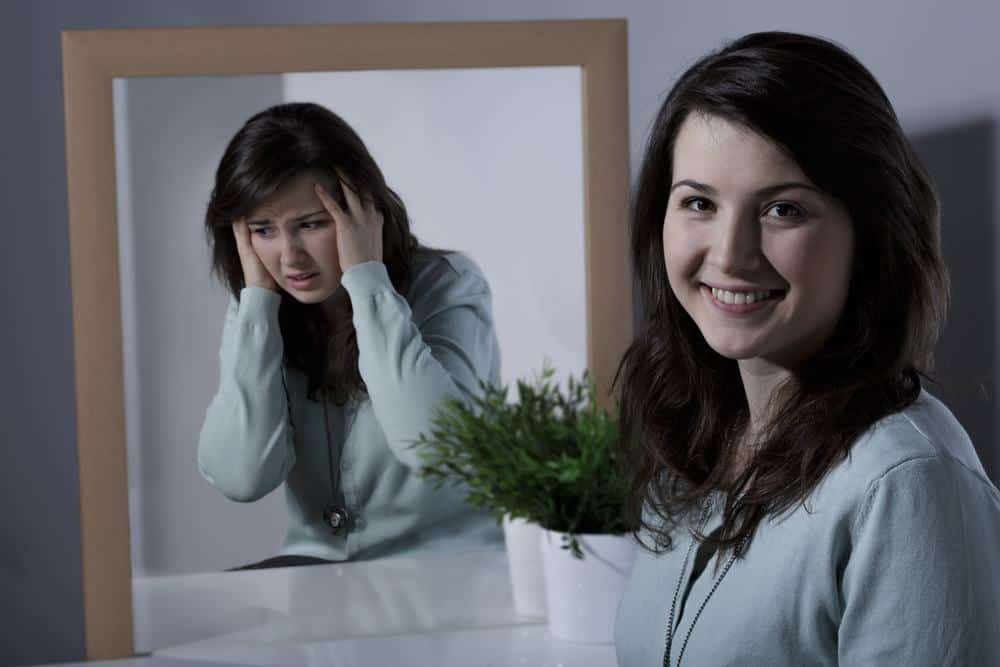 A woman smiling while her mirror image is depressed in the mirror.