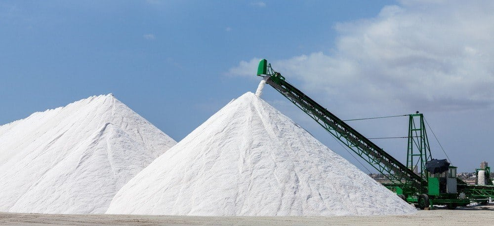 Two huge salt mounds at a factory.