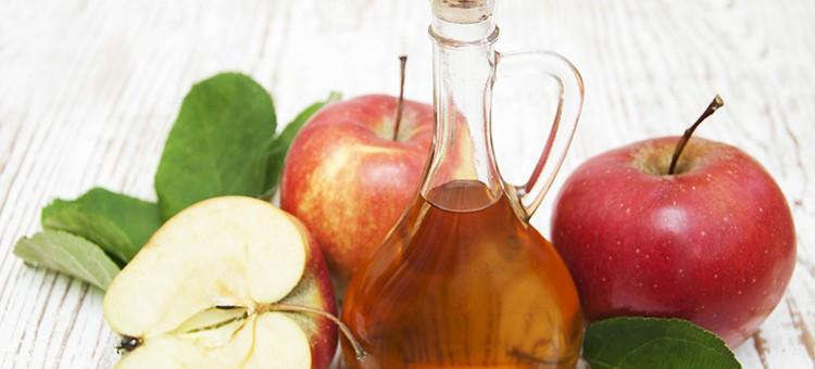 A bottle of apple cider vinegar next to some apples.