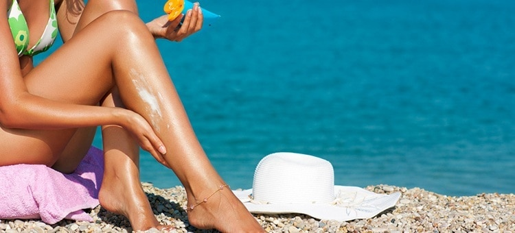 A woman applying sun lotion to her legs on a beach.