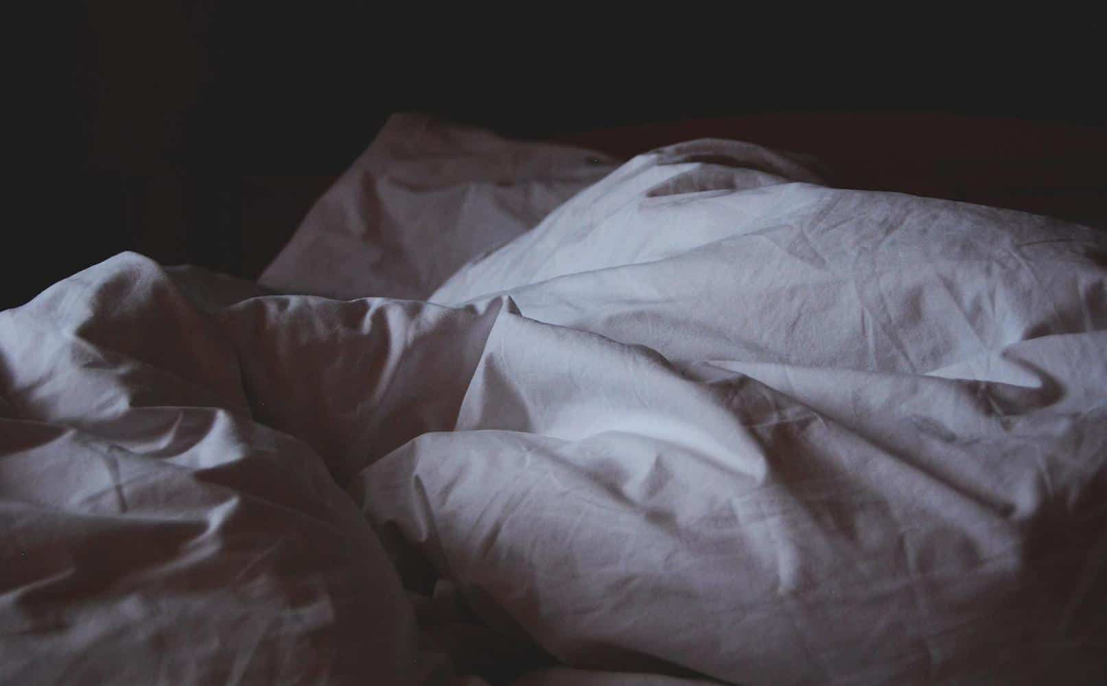Linen bed sheets in the dark.