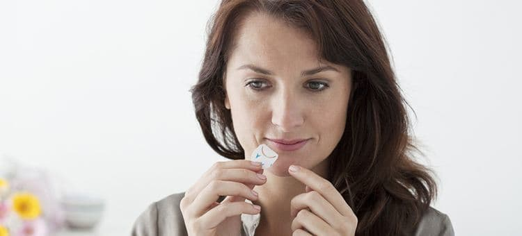 A woman treating a cold sore on her lips with some kind of ointment.