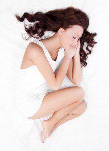 A woman enjoying sleep in a fetal position.