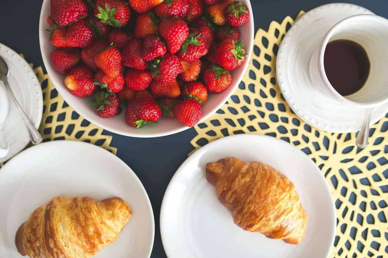 A light breakfast with croissants, a bowl of fruit, and coffee.