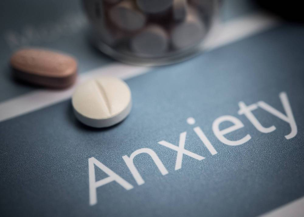 Anxiety written on a surface next to some tablets.