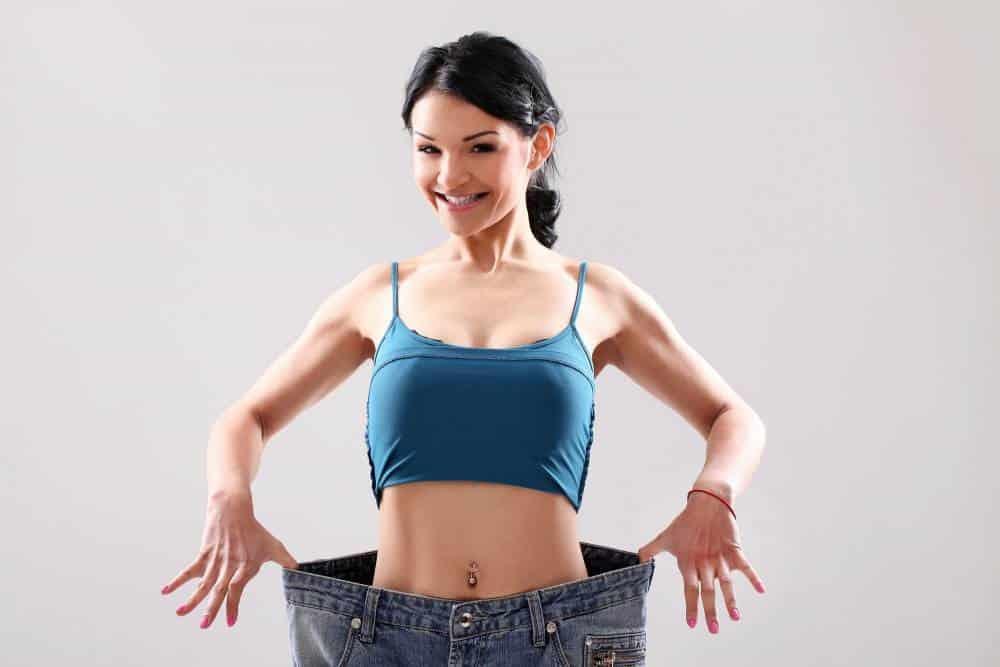 Una mujer en vaqueros de gran tamaño mostrando su pérdida de peso.