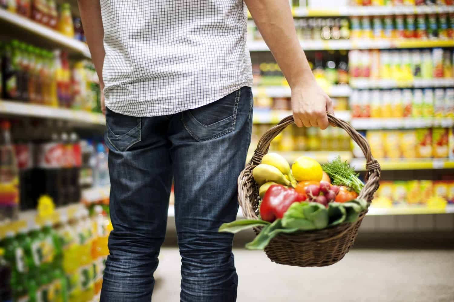 A man buying groceries at a store, holding a basket with fruit and vegetables.