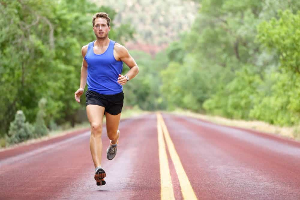 A runner running on a road in a forest.