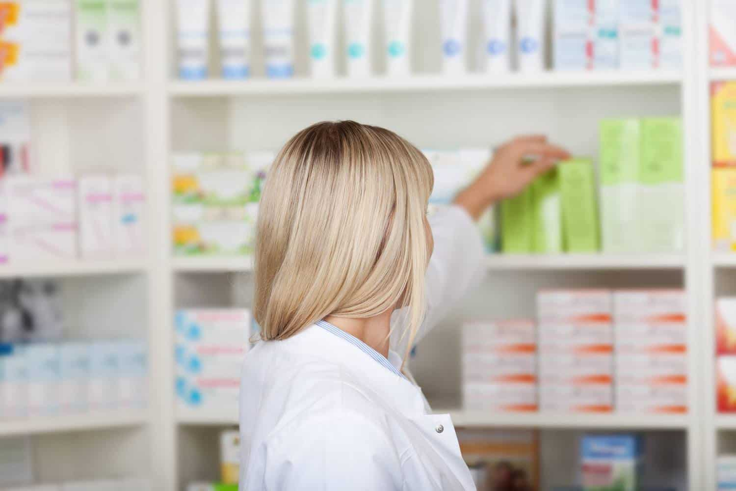 A pharmacist picking up medicine in a pharmacy.