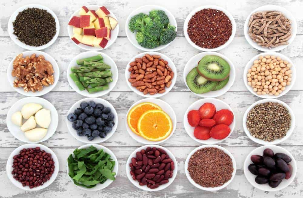 Varios tazones de frutas, verduras, legumbres y semillas.