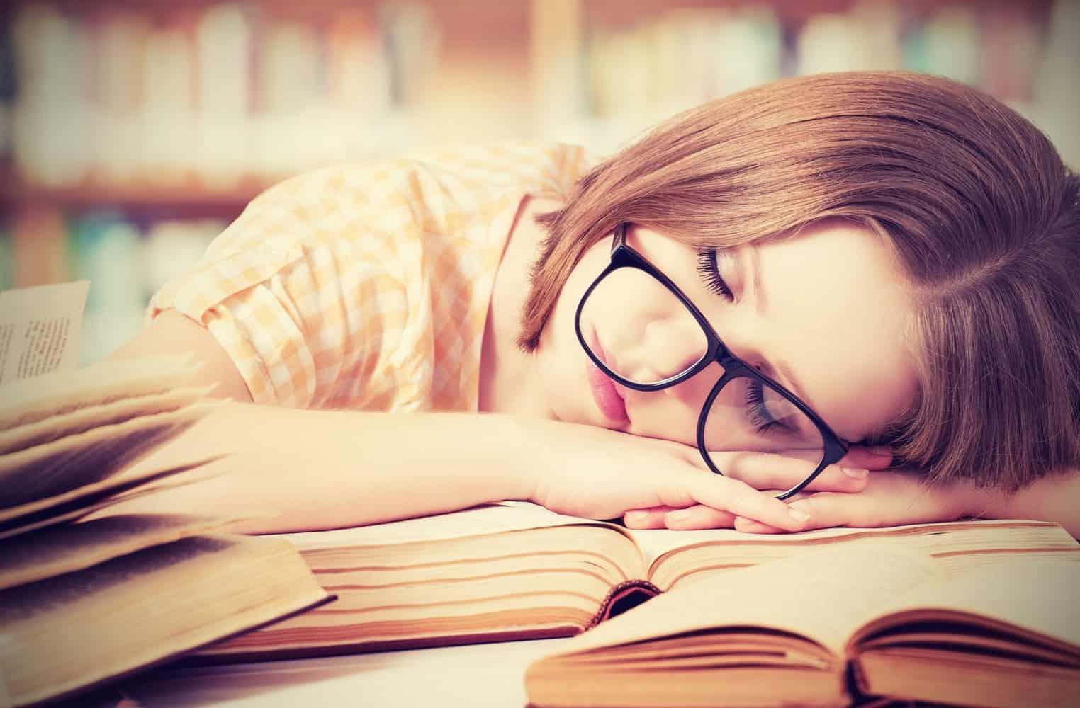 Una mujer durmiendo en una biblioteca.