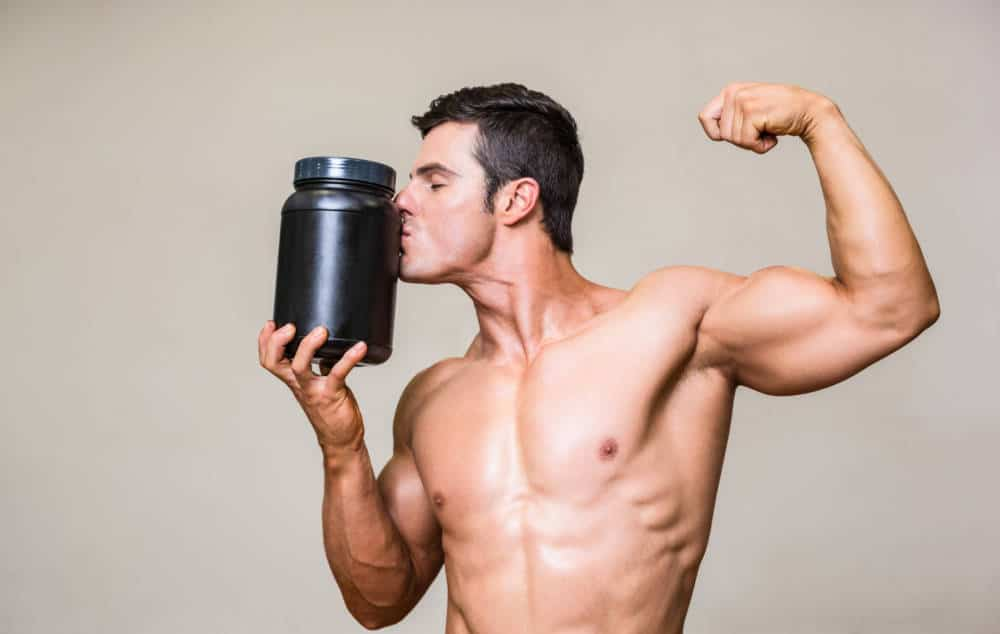 A muscular man kissing a large protein shake bottle.