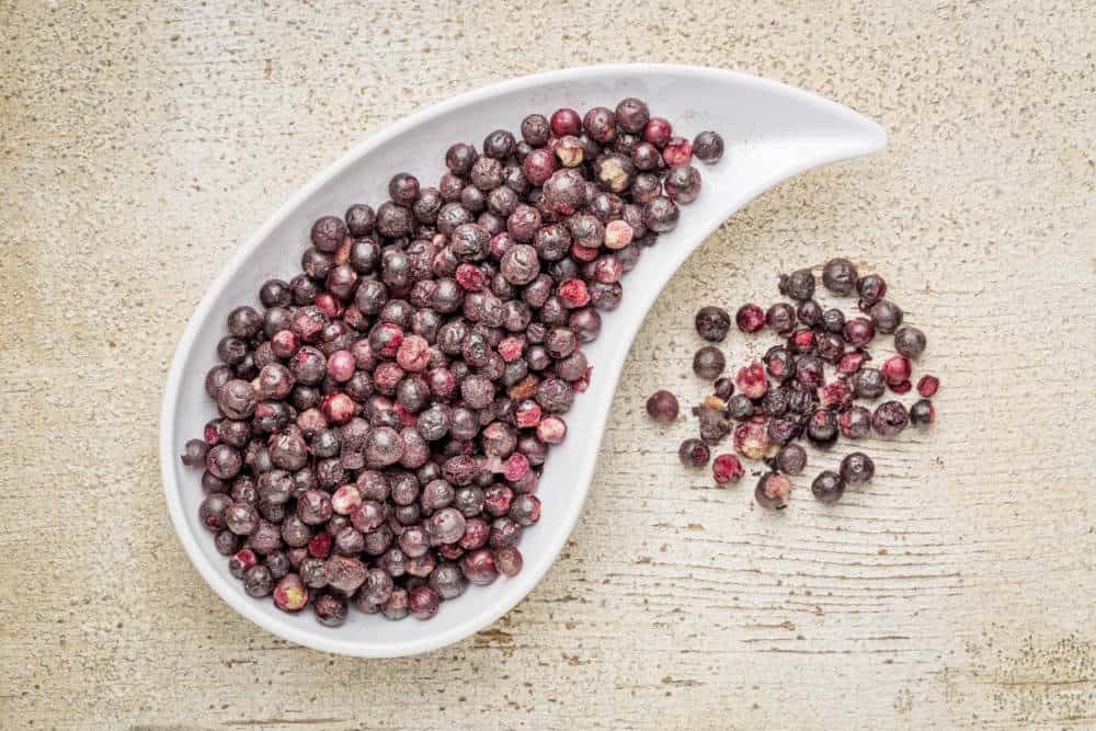 Freeze dried elderberries in a teardrop bowl against rustic barn wood. Elderberries are rich in antioxidants and minerals which make them perfect in battling the common cold.