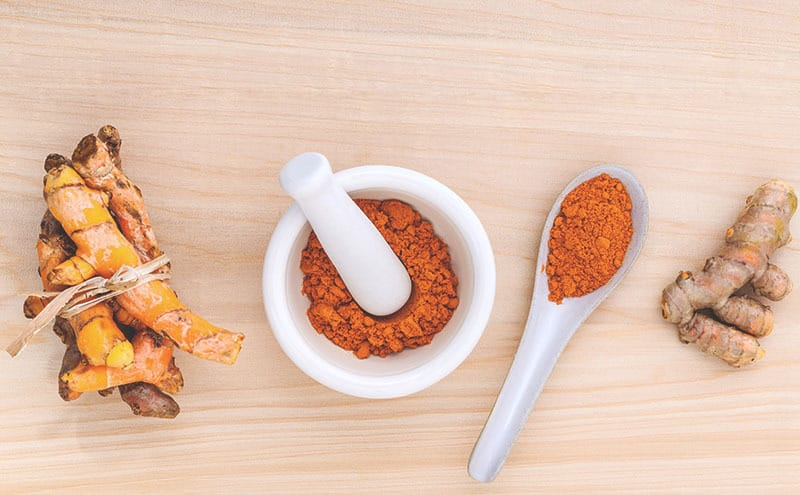 Pieces of turmeric tied together next to turmeric powder on a wooden table.
