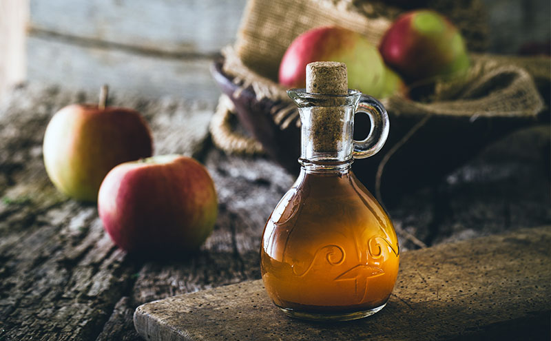 Apple cider vinegar in a rustic glass bottle on a flat piece of stone surrounded by some apples.