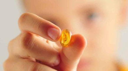 """Primer plano de una cápsula de aceite de pescado en manos de una persona. La leyenda de la imagen dice """"los muchos beneficios del aceite de pescado Omega-3"""""""